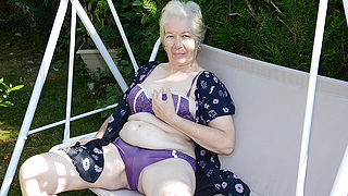 Naughty granny playing in the garden with her pussy